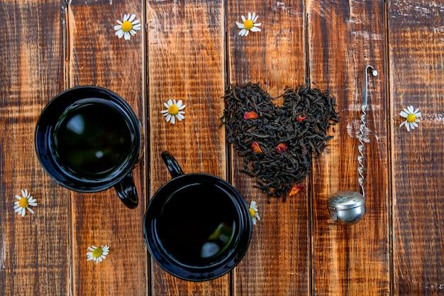 Deux tasses de thé près de feuilles sèches de thé noir en cœur