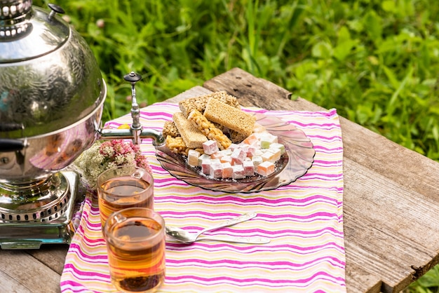 Deux tasses de thé et un samovar sur une table en bois avec divers bonbons