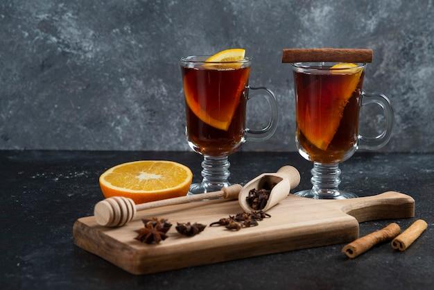 Deux tasses de thé en verre et avec des bâtons de cannelle et une louche en bois.