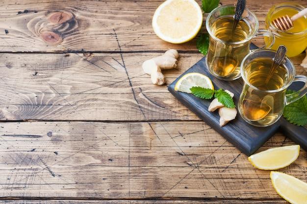 Deux tasses de tisane naturelle au gingembre, menthe citronnelle et miel sur une surface en bois.