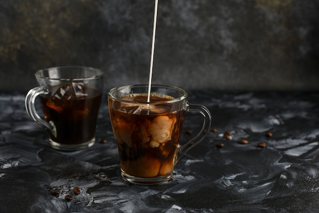 Deux tasses transparentes de café froid avec du lait