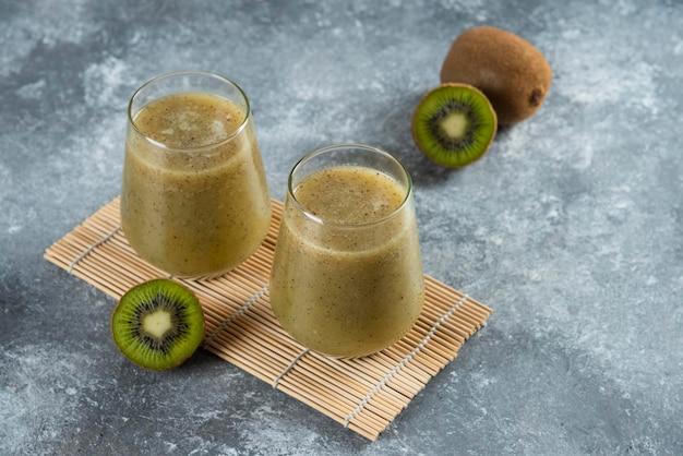 Deux tasses en verre de délicieux jus de kiwi sur une feuille de bambou.