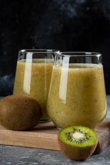 Deux tasses en verre de délicieux jus de kiwi sur planche de bois.