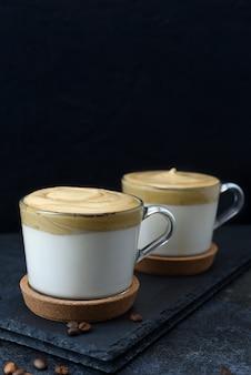 Deux tasses en verre avec du café dalgona sur fond sombre. espresso latte mousseux avec mousse de café sur fond noir.