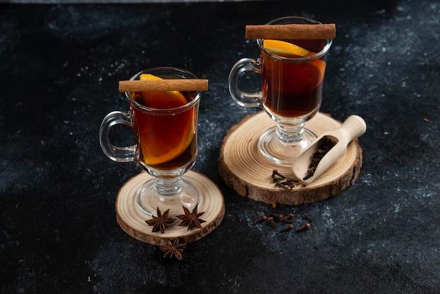 Deux tasses en verre avec du thé savoureux et des bâtons de cannelle.