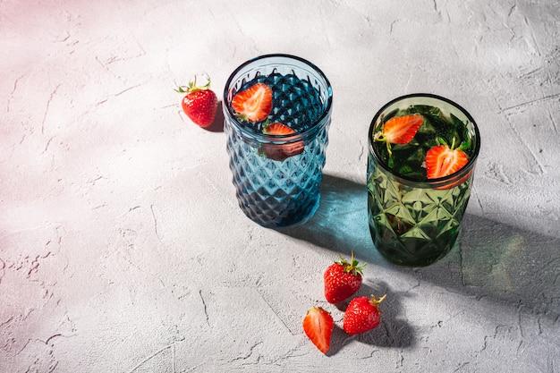 Deux tasses en verre géométrique vert et bleu avec de l'eau fraîche et des fraises