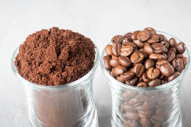 Deux tasses en verre avec grains de café et café moulu sur fond de béton clair