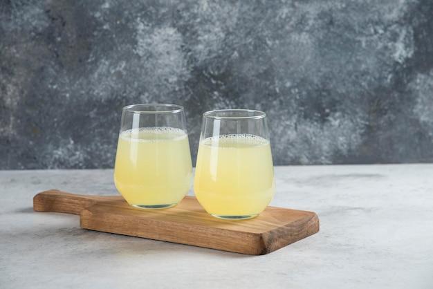 Deux tasses en verre de jus de citron sur une planche de bois.