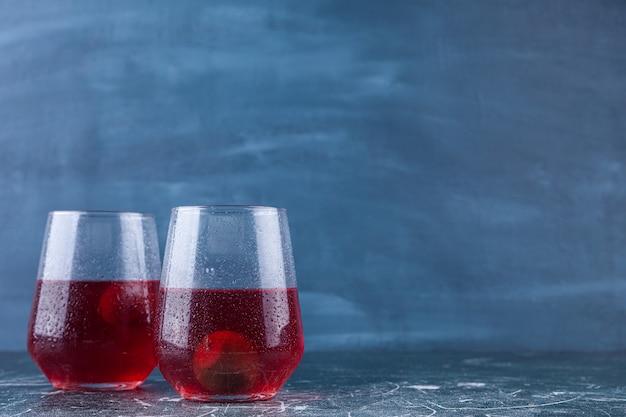Deux tasses en verre de jus de fruits frais placés sur un fond coloré.