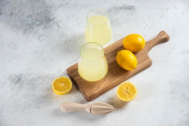 Deux tasses en verre de limonade savoureuse sur une planche de bois.