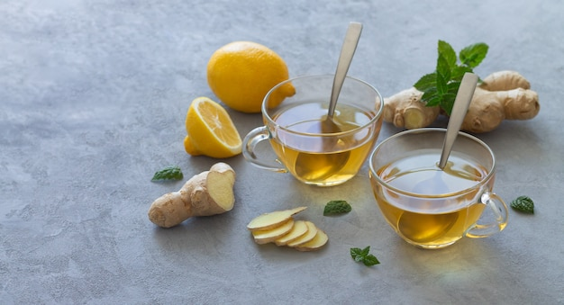 Deux tasses en verre de thé au gingembre avec des citrons et des feuilles de menthe. espace pour le texte