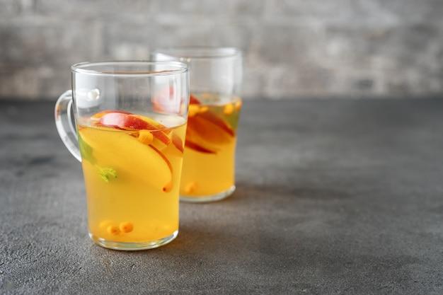 Deux tasses en verre avec thé à la pomme sur une surface grise