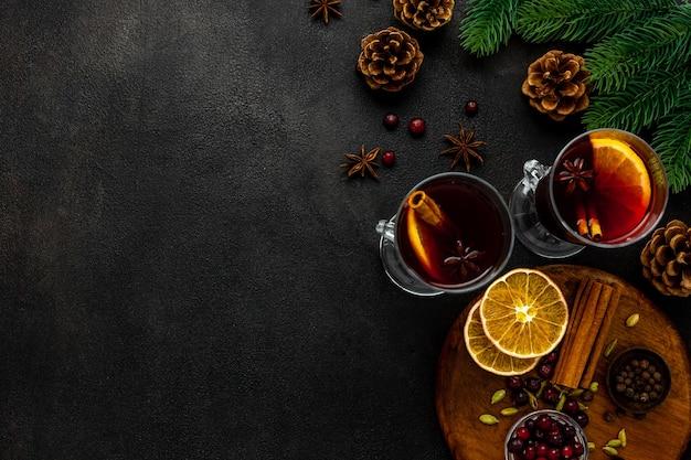 Deux tasses de vin chaud, d'épices et d'agrumes secs réchauffant la boisson de noël