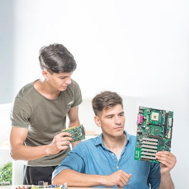 Deux techniciens masculins regardant la carte mère