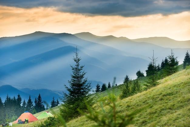 Deux tentes dans un camping avec vue sur les montagnes et le coucher du soleil
