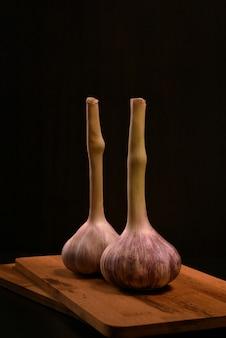 Deux têtes d'ail frais se tenant sur une planche à découper en bois sur un fond noir.