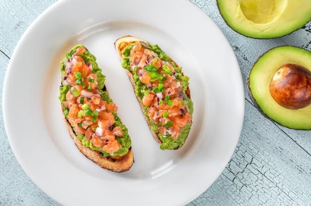 Deux toasts de guacamole et saumon sur plaque blanche