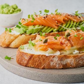 Deux toasts sandwich ouvert avec du fromage à la crème de saumon avocat tranches de concombre sur tableau blanc
