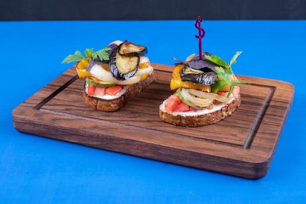 Deux toasts savoureux avec des légumes frits sur planche de bois.