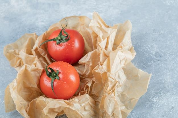 Deux tomates entières fraîches sur papier sulfurisé.