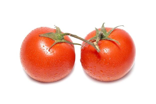 Deux tomates rouges avec des gouttes d'eau isolées