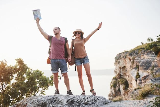 Deux touristes homme et femme avec des sacs à dos se tiennent au sommet du rocher et profitent du lever du soleil. voyager montagnes et côtes, liberté et concept de mode de vie actif