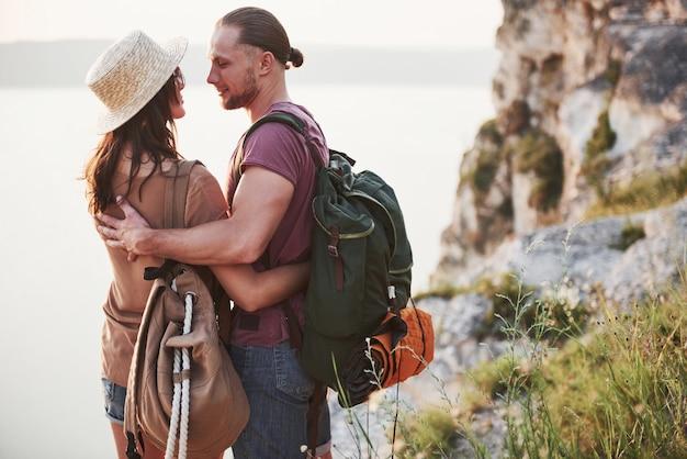 Deux touristes homme et femme avec des sacs à dos se tiennent au sommet de la montagne et profitent du lever du soleil. concept de vacances aventure voyage lifestyle
