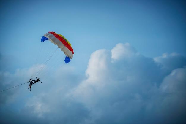 Deux touristes jouent au parachute ascensionnel dans le ciel en été.