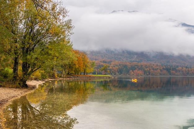 Deux touristes méconnaissables partent en canoë autour du pittoresque lac bohinj par une belle journée d'automne. les voyageurs kayak vers le rivage et les maisons de vacances se cachant entre les arbres changent de couleurs