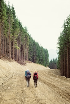 Deux touristes en randonnée à travers le chantier de construction d'une route de montagne. déforestation sur la pente