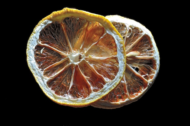 Deux tranches de citron en contre-jour. sur fond noir