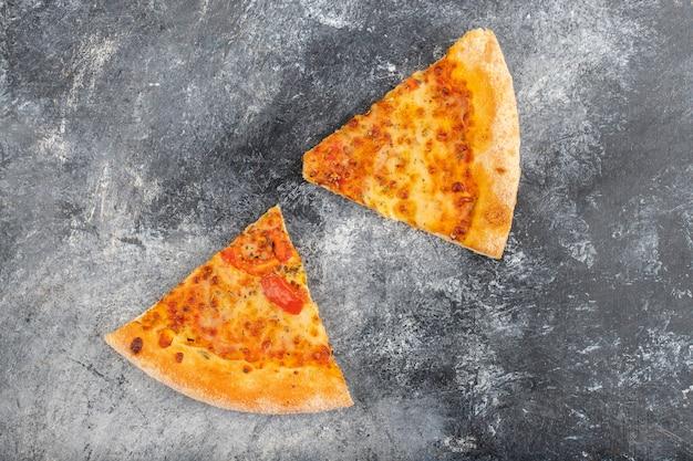 Deux tranches de délicieuses pizzas au fromage placées sur fond de pierre.