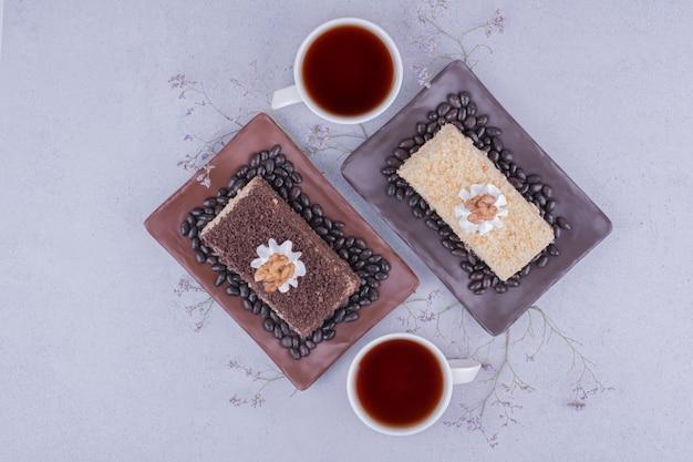 Deux tranches de gâteau medovic avec deux tasses de thé.