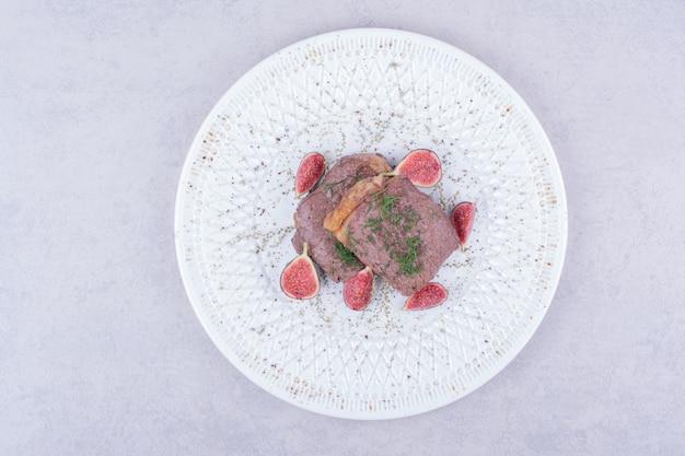 Deux tranches de steak aux herbes et épices dans une assiette blanche.