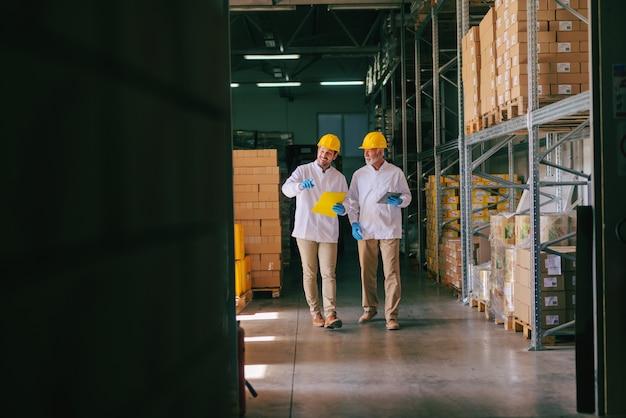 Deux travailleurs avec des casques sur la tête marchant dans l'entrepôt. tout autour des étagères et des boîtes.