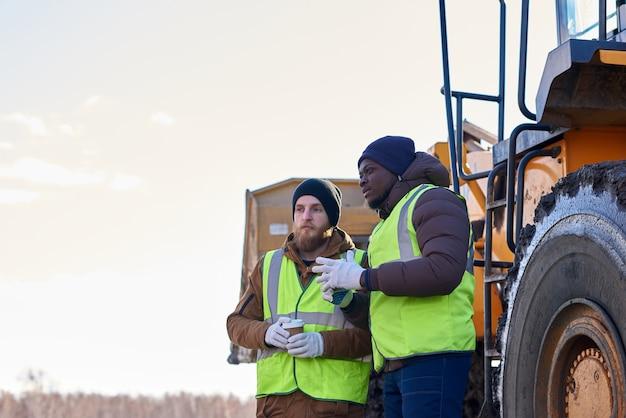 Deux travailleurs difficiles sur un site industriel à l'extérieur