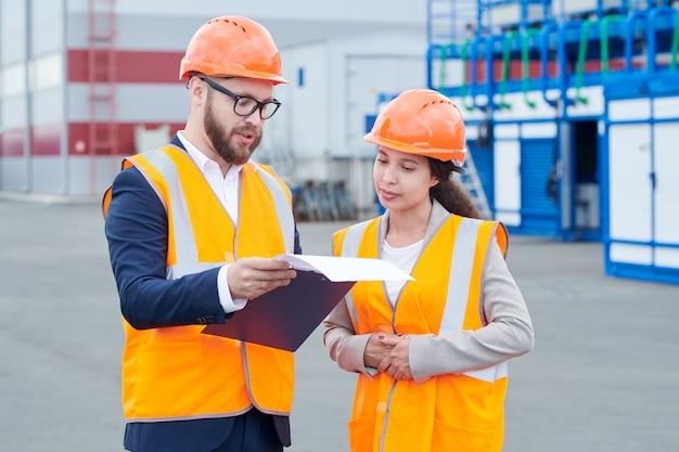 Deux travailleurs discutant du projet à l'extérieur