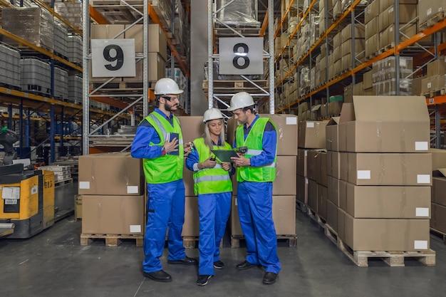 Deux travailleurs masculins et féminins portant un uniforme de protection debout devant des colis regardant le presse-papiers.
