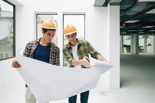 Deux travailleurs avec plan de construction