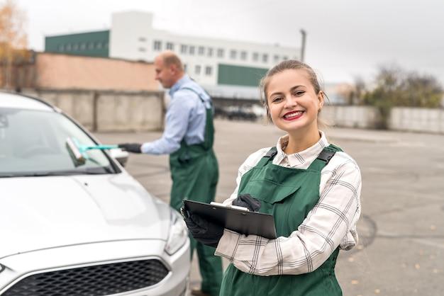 Deux travailleurs sur le service de voiture posant près de la voiture