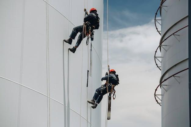 Deux travailleurs de sexe masculin contrôlent la corde d'oscillation vers le bas, l'inspection de l'accès à la corde du réservoir de l'épaisseur du pipeline et du gaz du réservoir