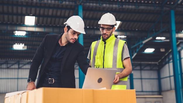 Deux travailleurs d'usine travaillant et discutant du plan de fabrication dans l'usine