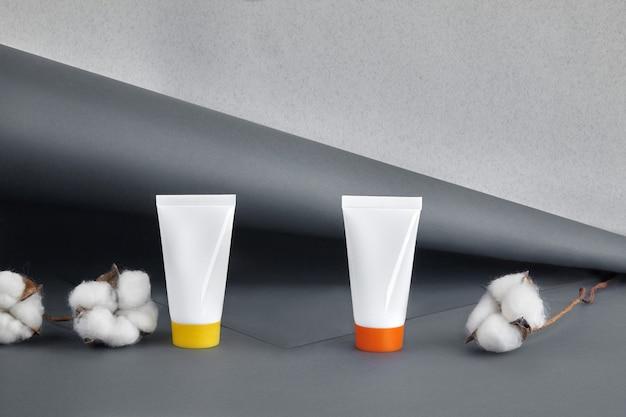 Deux tubes cosmétiques blancs avec des bouchons colorés