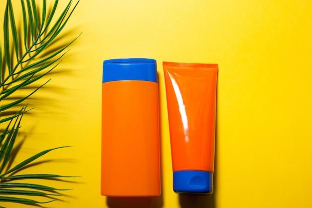 Deux tubes avec des écrans solaires simulés sur un fond d'été jaune. protection uv de la peau avec un filtre spf, un shampooing-soin capillaire et un revitalisant. un bronzage en toute sécurité sur la plage. mise à plat - station balnéaire sur la mer.