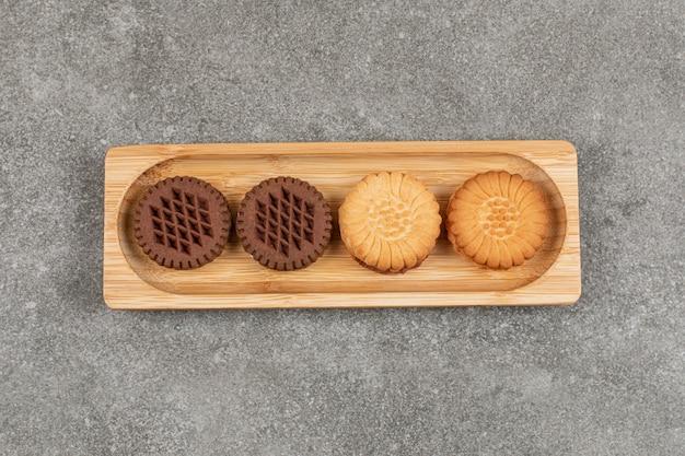 Deux types de biscuits sandwich sur plaque en bois.
