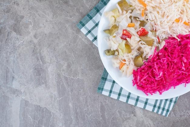 Deux types de choucroute et cornichons sur plaque blanche avec nappe.