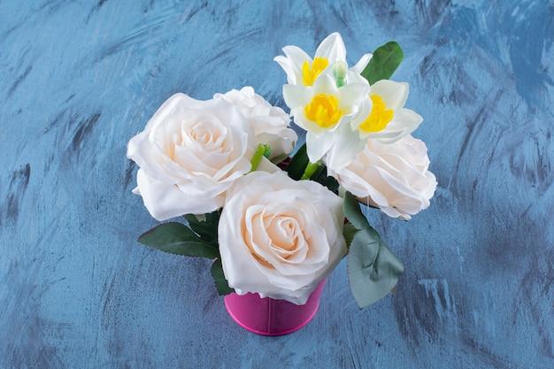 Deux types de fleurs placées dans un seau rose sur bleu.