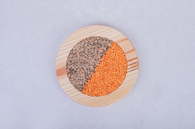Deux types de haricots crus et de lentilles dans une assiette en bois.