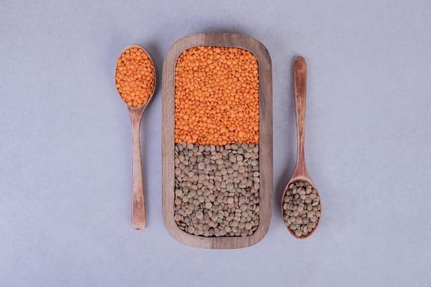 Deux types de haricots et de lentilles crus dans une assiette en bois avec des cuillères.
