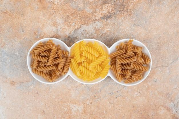 Deux Types De Macaronis Non Cuits Sur L'espace De Marbre Photo gratuit